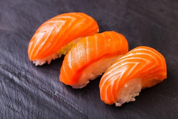Close-up de sake sushi com salmão em um fundo de ardósia preta
