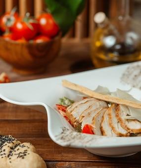 Close-up de salada caesar com fatias de frango grelhado, parmesão e pão