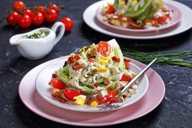 Close-up de salada de fatias de iceberg coberta com molho de queijo azul, bacon frito crocante, tomate cereja, ovos cozidos, cebolinha em pratos em uma mesa de concreto, vista da paisagem Foto Premium