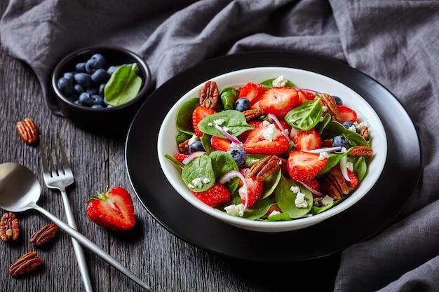 Close-up de salada de verão de morangos, mirtilos, espinafre, nozes pecan e queijo feta esfarelado em uma tigela branca sobre uma mesa de madeira escura com um pano cinza, visão horizontal de cima, macro