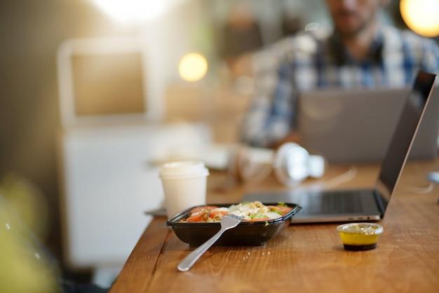 Close up de salada e café no espaço de trabalho co