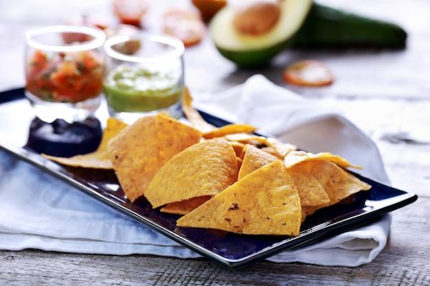 Close up de salgadinhos de milho leves e crocantes servidos com salsa e guacamole