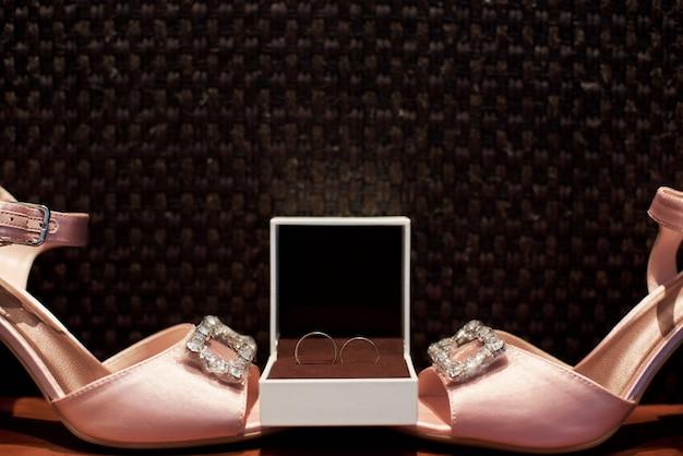 Close-up de sandálias cor de rosa lindas e anéis de ouro de casamento com diamantes