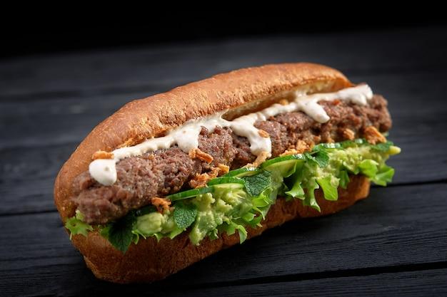 Close-up de sanduíche de kebab em fundo preto de madeira