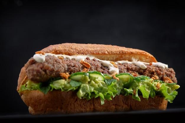 Close-up de sanduíche de quibe no espaço de madeira preto