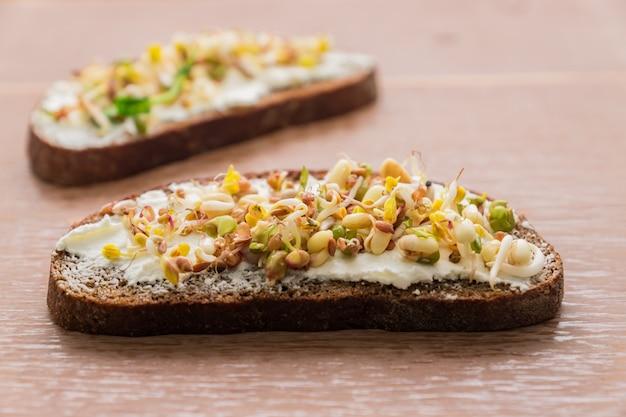 Close-up de sanduíches de pão de centeio com creme de queijo e brotou feijão mungo, nozes, girassol e linho na madeira
