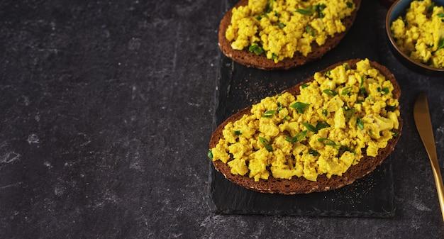 Close-up de sanduíches de salada de ovo vegan colorido sobre fundo preto