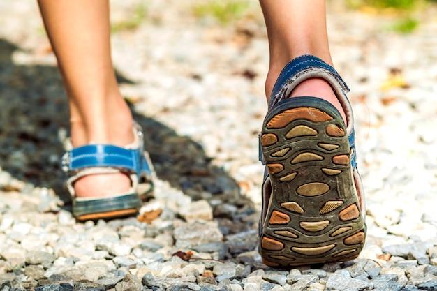 Close-up de sapatas do esporte na trilha andando nas montanhas em pedras, atividade ao ar livre