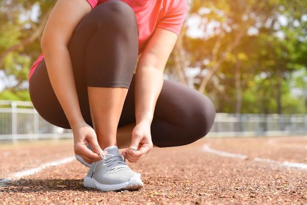 Close up de sapatas running do laço da jovem mulher para movimentar-se ao ar livre. conceito de estilo de vida saudável.