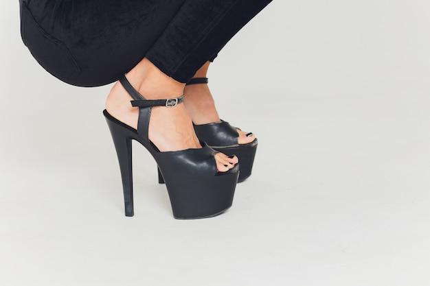 Close-up de sapatos com sapatos de salto altos nas pernas
