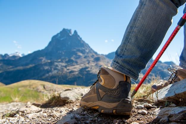 Close-up de sapatos de alpinista, o pic ossau no fundo