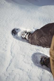 Close up de sapatos de esquiador em paisagem de neve