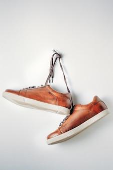 Close-up de sapatos masculinos de couro marrom pendurar na unha em fundo branco