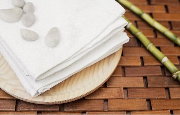 Close-up de seixos; toalha e bambu planta na mesa de madeira