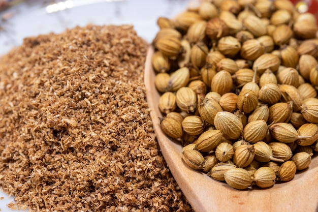 Close-up de sementes de coentro secadas em uma colher com pó de coentro, ervas indianas da culinária.
