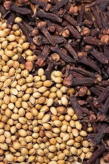 Close-up de sementes de coentro secas e cravo, erva picante seca para aroma de alimentos e medicamentos naturais, ingrediente em especiarias indianas