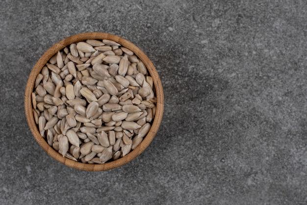 Close up de sementes de girassol descascadas sobre superfície cinza
