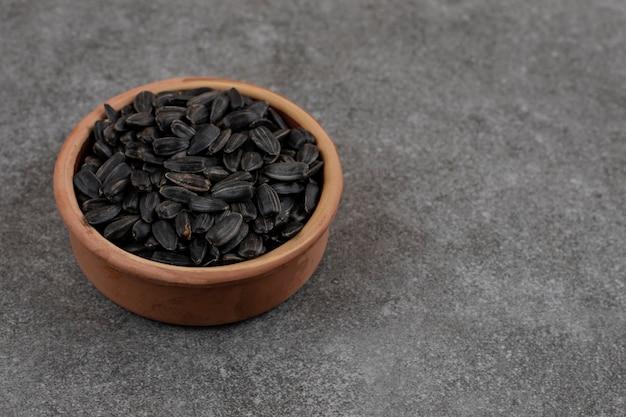 Close up de sementes de girassol em uma tigela de cerâmica sobre uma superfície cinza