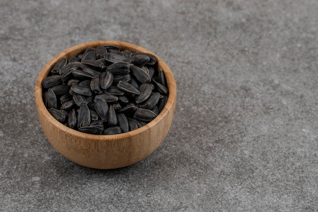 Close up de sementes de girassol em uma tigela de madeira sobre uma superfície cinza