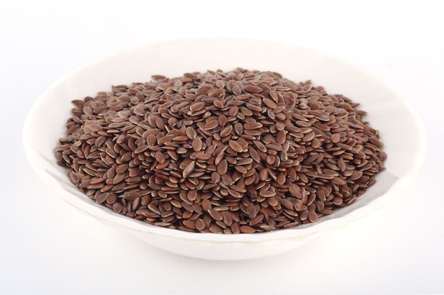 Close up de sementes de linho em uma chapa branca isolada na superfície branca