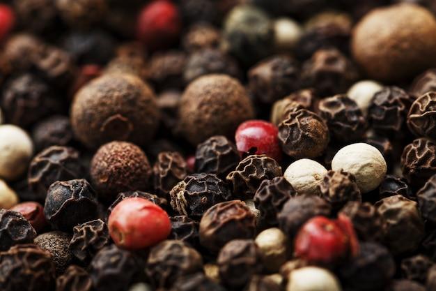 Close-up de sementes de pimenta em tela inteira. pimenta preta, branca, verde e rosa.