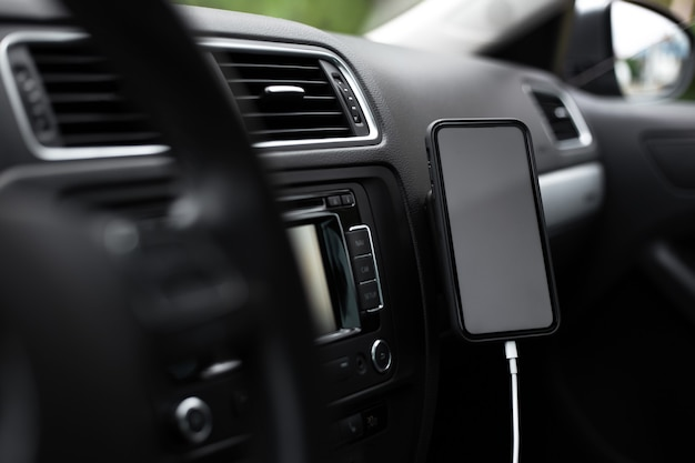 Close-up de smartphone moderno com tela vazia em carga dentro do carro.
