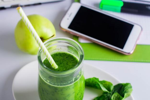 Close-up de smoothie verde saudável no local de trabalho, mesa de trabalho com notebook