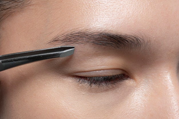 Close-up de sobrancelha removendo para beleza