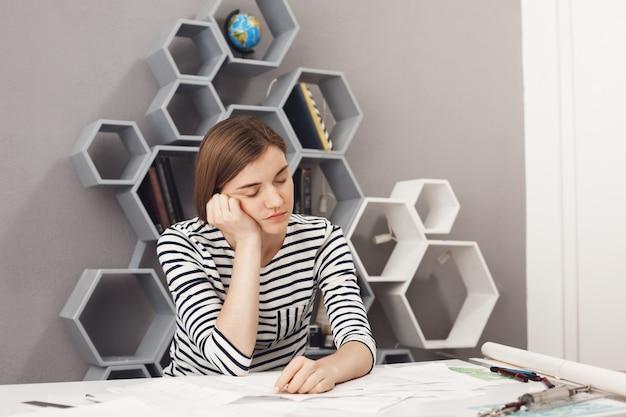 Close-up de sonolento jovem gerente feminino bonito, com cabelos escuros e camisa listrada, segurando a cabeça com a mão