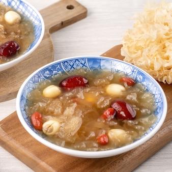 Close up de sopa doce tradicional chinesa de fungo branco de neve com semente de lótus, tâmaras vermelhas (jujuba) e wolfberry (goji berry, gojiberry) em branco