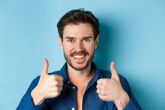 Close-up de sorridente homem bonito mostrando os polegares, elogiando o bom trabalho, recomendando a empresa, de pé sobre fundo azul.