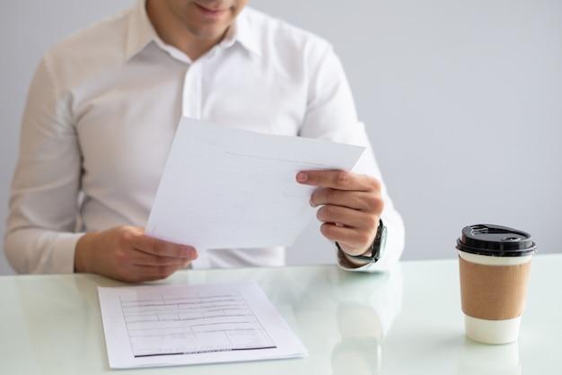 Close-up, de, sorrindo, jovem, homem negócios, olhar documento