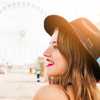 Close-up, de, sorrindo, mulher jovem, com, chapéu preto, ligado, dela, cabeça