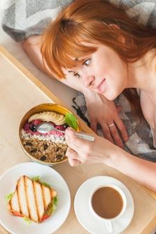 Close-up, de, sorrindo, mulher jovem, comer, granada aveia
