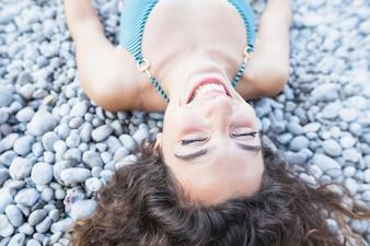 Close-up, de, sorrindo, mulher jovem, deitando, ligado, seixos, com, olhos fecharam