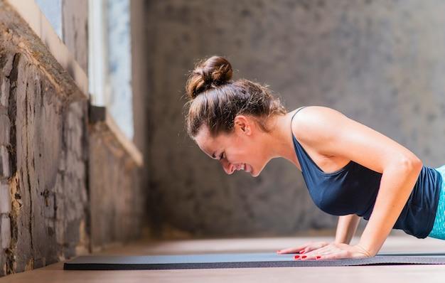 Close-up, de, sorrindo, mulher jovem, fazendo, flexões