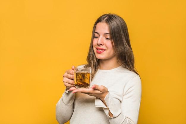 Close-up, de, sorrindo, mulher jovem, olhar, chá herbário, em, a, copo copo