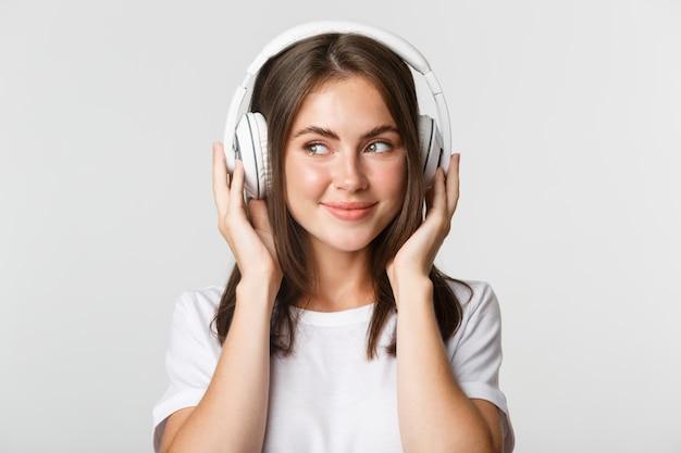Close-up de sorrir música atraente menina morena em fones de ouvido, desfrutando de podcast interessante.