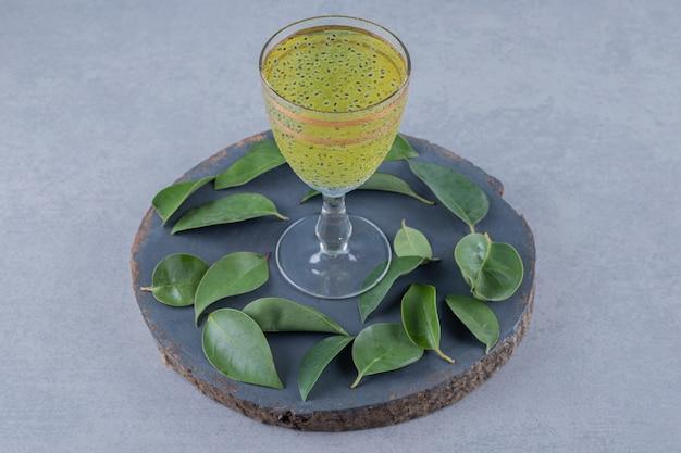 Close up de suco de pêra fresco com folhas em uma placa de madeira