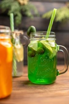 Close-up de sucos frescos orgânicos em garrafas servidas com tubos e frutas em uma mesa de madeira marrom