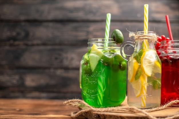 Close-up de sucos naturais de frutas orgânicas em garrafas servidas com tubos em uma tábua de madeira