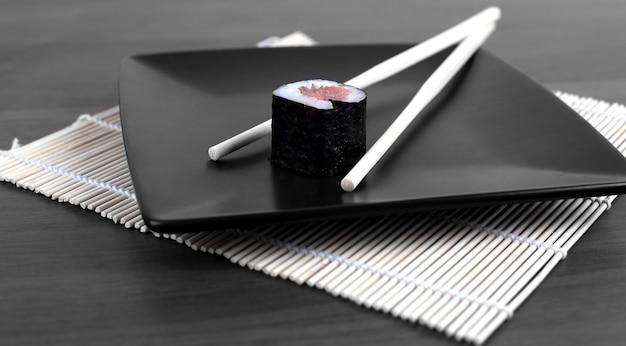 Close-up de sushi e pauzinhos em uma mesa de madeira. foto com espaço de cópia