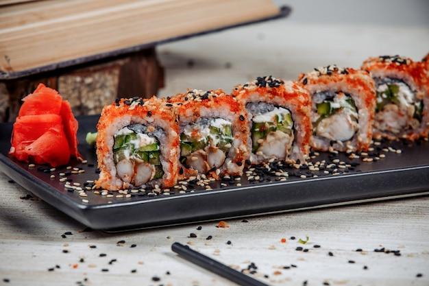 Close-up de sushi rolls com camarão, pepino, coberto com tobiko vermelho