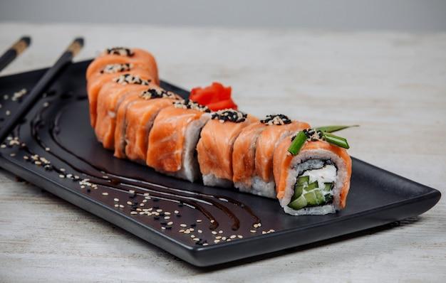 Close-up de sushi rolos conjunto coberto de salmão com pepino e creme
