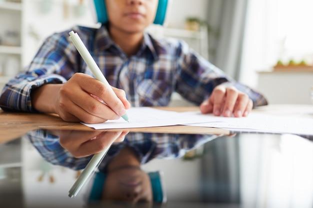 Close-up de tablet digital na mesa com criança sentada e fazendo anotações no caderno