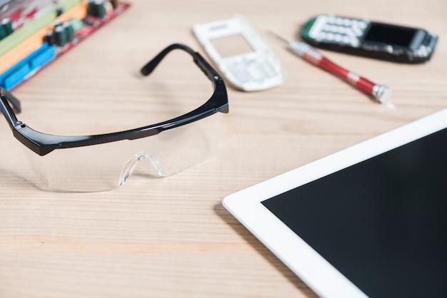 Close-up de tablet digital; óculos de segurança e celular quebrado em fundo de madeira