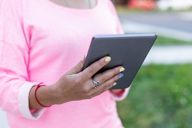 Close-up de tablet são usados por mulher na rua de verão. visão traseira.
