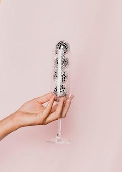 Close-up de taça de champanhe com bolas de discoteca