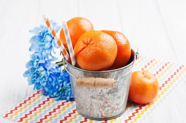 Close-up de tangerinas frescas em um balde de lata