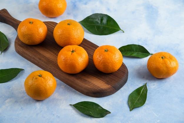 Close up de tangerinas orgânicas frescas na placa de madeira